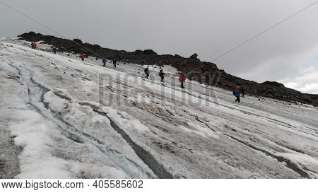 Mountaineers Walking Down A Hill Along A Snowy Slope And A Cold Flowing Stream. Clip. Western Alps,