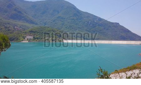 Top View Of Blue Reservoir In Mountains. Clip. Behind The Trees Is Beautiful Landscape With Turquois