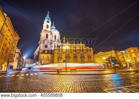 Lesser Town In Prague By Night. Cobbled Street And Illuminated Buildings With Baroque Dome Of St Nic