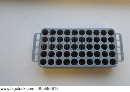 Gray Cassette With Many Holes. Seedling Mold. Planting New Plants In The Ground. Planting Gardeners,