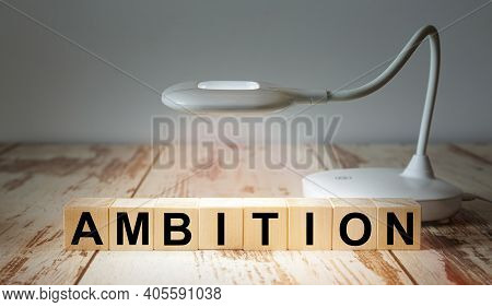 A Table Lamp Illuminates Wooden Blocks With The Word Ambition. Business Concept