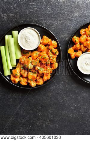 Cauliflower Buffalo Wings With Celery And Sauce On Plates Over Black Stone Background With Free Text