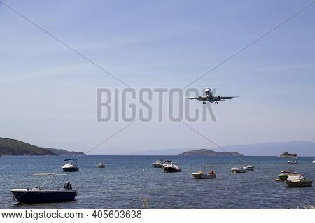 Skiathos, Greece - August 13, 2019. Aeroplane Flying In Over Skiathos Old Harbour, Skiathos Town, Gr