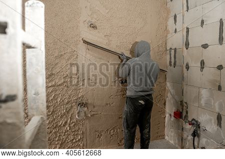 Worker Polishes The Wall After Machine Plaster. Walls With Gypsum Plaster Or Cement Plaster. Plaster