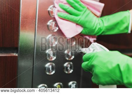 Antiviral Disinfection With An Aerosol Sanitizer Of The Elevator Buttons, With Female Hands In Glove