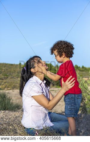 Child Performing Act Of Love Towards His Mother With A Caress On The Face, Happy And Smiling Mother
