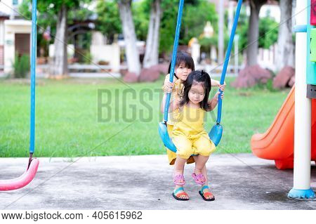 Two Cute Asian Little Sisters Playing Blue Swinging. The Eldest Sister Swings The Player For Her Sis