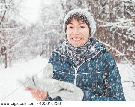 Smiling Woman With Gloves And Knitted Hat. Fun In Snowy Winter Forest. Woman Laughs As She Walks Thr