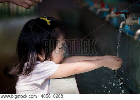 Adorable Asian Little Girl Is Washing Hands With Water Opened By A Tap. To Keep The Palm Clean And E