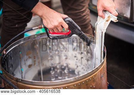 Asian Man's Hand Held A High-pressure Spray Gun Was Spraying Water Onto The Stain With The Equipment