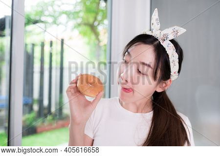 Portrait Of Caucasian People Young Asian Woman Stick Out Tongue Lick Lips, Wanting To Eat The Donuts