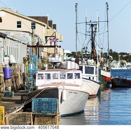 Portland, Maine, Usa - 25 July 2020: Fishing And Lobster Boats Docked In An Inlet Behind Stores And
