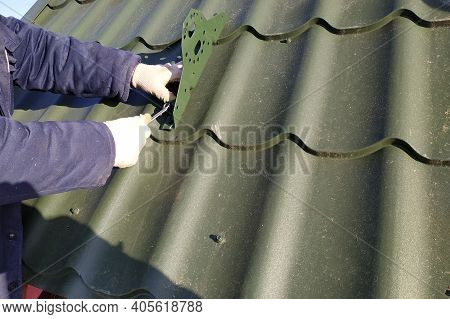 In The Cold Season, The Worker Fastens The Roof Elements To The Roof