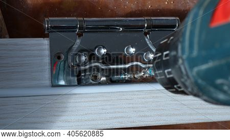 Shiny Metal Fastener With Holes On The Light Wood Strip Under The Pressure Of The Tool Screwing The
