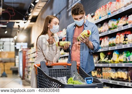 Woman In Medical Mask Pointing With Hand Near Boyfriend With Packages Of Groceries In Store.