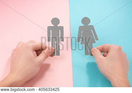 Hands Holding Paper Figures Of Man And Woman
