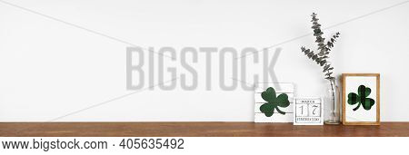 St Patricks Day Decor On A Wood Shelf. Shabby Chic Wood Signs, Calendar And Green Branches Against A
