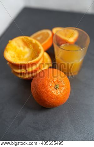 Glass Of Squeezed Orange Juice And Peels, On Gray Table.