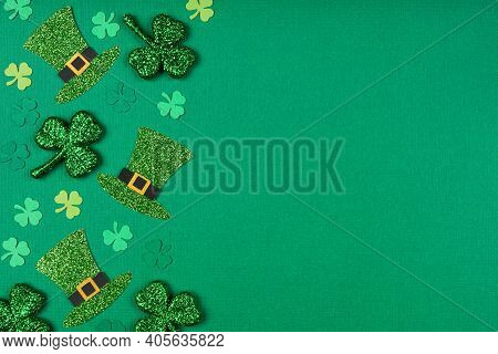 St Patricks Day Shamrock And Leprechaun Hat Side Border. Top Down View Over A Green Paper  Backgroun