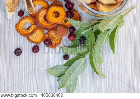 Sliced Dried Dehydrated Apples, Apricots And Bananas, Dried Cherries In A Glass Jar, Mint Leaves On