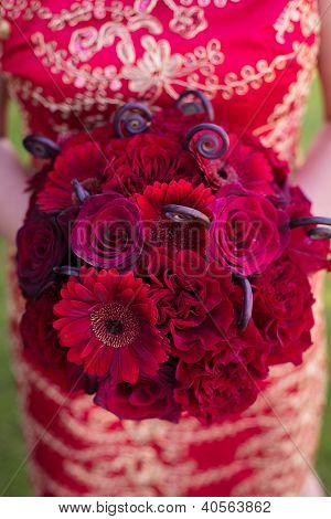 Bride in Red Dress Holding Red Roses and Gerber Daisy Bouquet