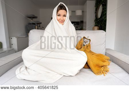 Woman Feeling Cold. Freezing Woman And Cat Under A Plaid Have Cold On The Sofa At Home. Warming Unde