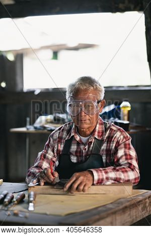 Carpenter Working On Wood In Carpentry Shop. The Man Works In A Carpentry Shop