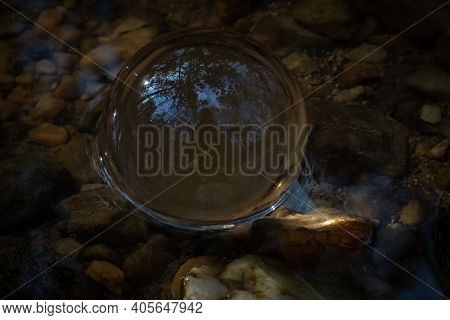 Sunlight Converges Through A Glass Or Crystal Ball, And The Beams Are Visible Under The Surface Of S