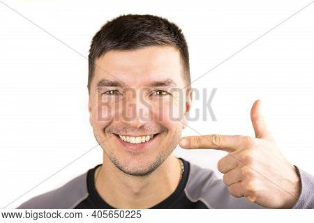 Beautiful Male Snow-white Smile And Lips Of Caucasian Appearance Close-up. Points Finger At The Teet