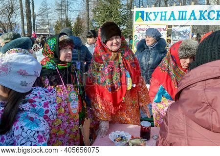 Chelyabinsk, Russia, March 2, 2014. Russian national holiday of farewell to winter. Slavic holiday Maslenitsa. Women in national costumes treat people to tea.