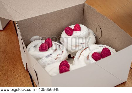 Exquisite Cinnamon Roles With White Icing And Red Fruits On Top Inside A White Box On A Wooden Table
