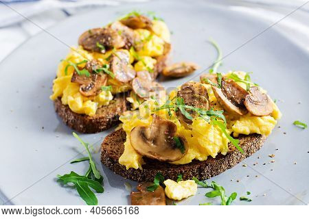 Scrambled Eggs And Fried Mushrooms On Bread. Homemade Breakfast Or Brunch Meal - Scrambled Eggs And
