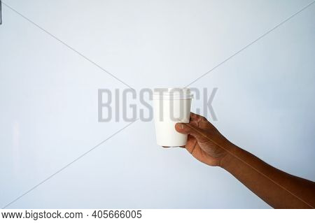 The Hand Of A Dark-skinned Man Holds A Disposable Cup For Coffee