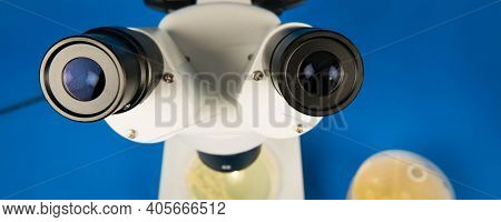 Scientific microscope and petri dishes for scientific research on blue background