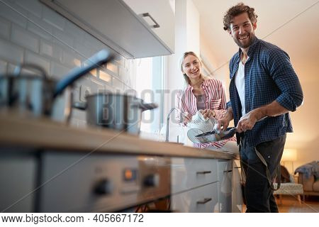 Young couple doing housework and posing for a photo in a relaxed atmosphere in the kitchen. Kitchen, housework, home, relationship