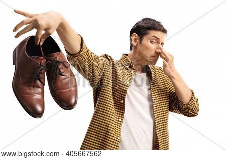 Man blocking his nose and holding a pair of smelly shoes isolated on white background