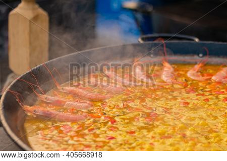 Process Of Cooking Paella With Shrimp, Mussel, Rice, Saffron In Huge Paella Pan At Summer Outdoor Fo