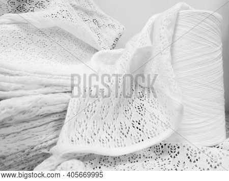 White Cotton Yarn In Bobbins And Knitwear Made From This Yarn In Production.