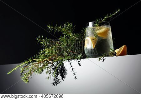 Alcohol Drink (gin Tonic Cocktail) With Lemon, Juniper Branch, And Ice On A Black Background, Copy S