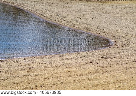 Beautiful Lake Shoreline Curves Gently. Water Is Calm With Small Waves And Ripples Against The Brown