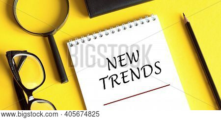 New Trends Text Written On Notebook With Glasses, Magnifier End Pen On Yellow Table. Main Trend Of C