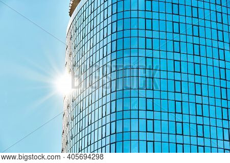 Stylish Skyscraper With Glass Facade Against Clear Blue Sky