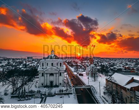 Aerial View Of The Cathedral And Church In Snow-covered Small European City At Bright Winter Sunset