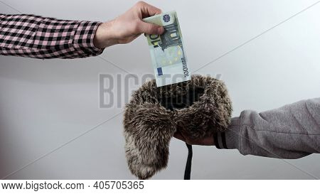 Putting money in a hat to a beggar on a white background, banknotes, finances, a homeless person asks for money, a man in a difficult financial situation.