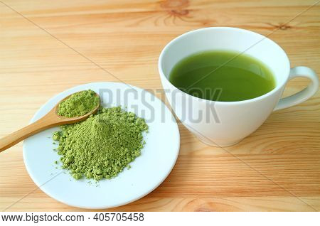 Plate Of Matcha Tea Powder With A Cup Of Hot Matcha Green Tea On Wooden Table