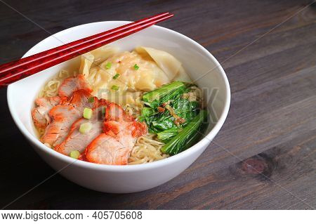 Closeup A Bowl Of Wonton Dumpling And Egg Noodle Soup With Roasted Pork Isolated On Wooden Table