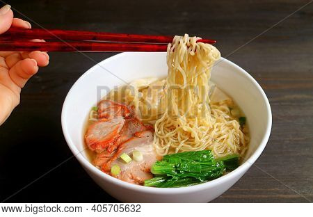 Woman's Hand Grabbing Delectable Chinese Egg Noodle With Chopsticks