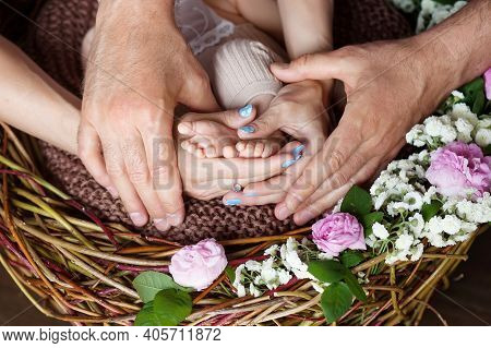 Baby Feet In Parents Hands. Tiny Newborn Baby's Feet On Parents Shaped Hands Closeup. Parents And Th