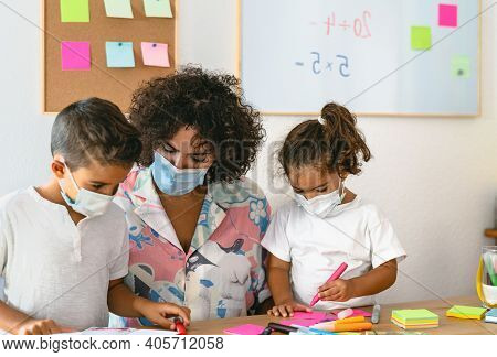 Teacher With Children Wearing Face Mask In Preschool Classroom During Corona Virus Pandemic - Health