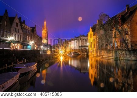 Iconic Fairytale View Of The Canals Of Bruges, During The Rain. Nepomucenus Bridge And Church Of Our
